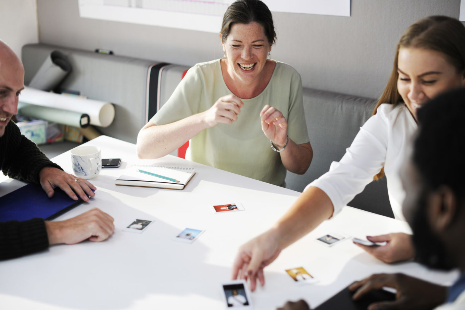 people-around-desk-looking-at-cards-working