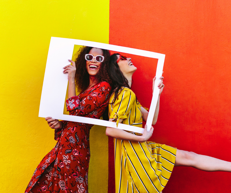 Two females dressed in yellow and orange with a Instagram shopping cut out