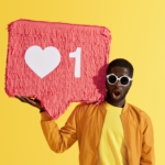 A man dressed in yellow holding a social media symbol used for influencer marketing